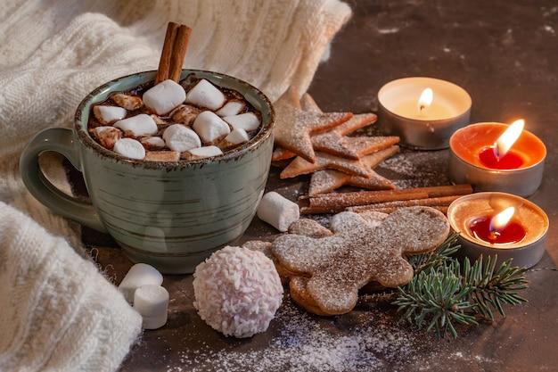 Composição de natal atmosférica: uma xícara de chocolate com velas de marshmallows e biscoitos de gengibre
