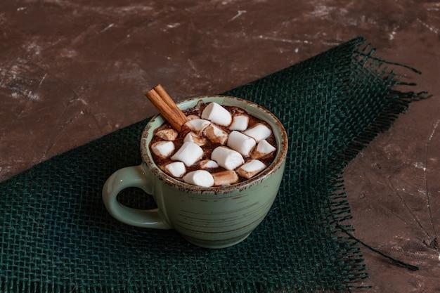 Composição de natal atmosférica, uma xícara de chocolate quente com marshmallows, biscoitos de gengibre, doces ...