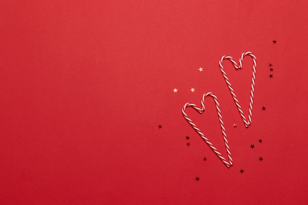 Composição de natal. bastões de doces em forma de amor e estrelas sobre fundo vermelho. natal, inverno, ano novo conceito. vista plana, vista superior
