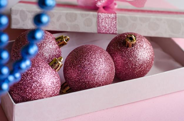 Composição de natal. caixa de presente aberto com enfeites em rosa pastel. fechar-se. .