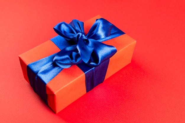 Composição de natal. caixa de presente vermelha com fita azul onred. vista de cima. um presente de natal