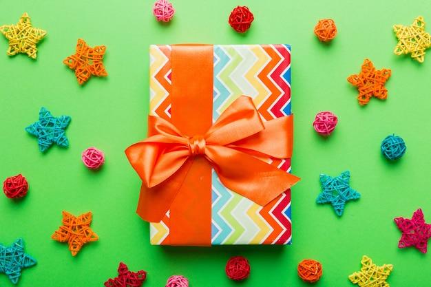 Composição de natal. caixa de presentes com decorações de ano novo em fundo colorido. natal, inverno, conceito de ano novo. camada plana, vista superior, espaço de cópia.