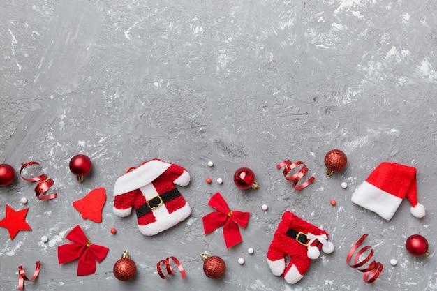 Composição de natal. chapéu de natal calças casaco de pele de papai noel na cor de fundo. camada plana, vista superior, espaço de cópia. modelo de cartão postal de natal