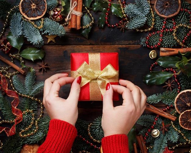 Composição de natal com as mãos segurando uma caixa de presente