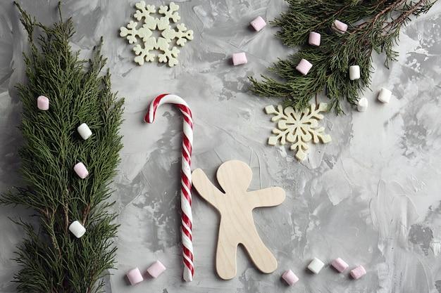 Composição de natal com bastão de doces e enfeites em plano de fundo texturizado