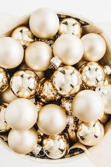 Composição de natal com bolas de decoração dourada na superfície branca. vista do topo