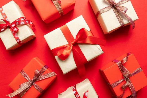 Composição de natal com caixas de artesanato vermelho festivo e padrão de fitas vermelhas.