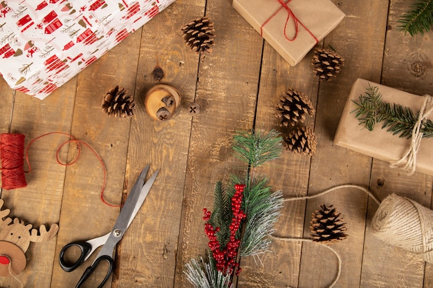 Composição de natal com caixas de presente, bobina de fita, tesoura, galhos de mordida e elementos de madeira na madeira