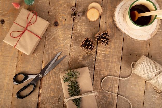 Composição de natal com caixas de presente, bobina de fita, tesoura, morder galhos na madeira