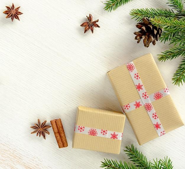 Composição de natal com caixas de presente embrulhadas em papel kraft, ramos de abeto com cone e especiarias de natal em pau de canela, estrelas de anis em fundo branco de madeira. copie o espaço