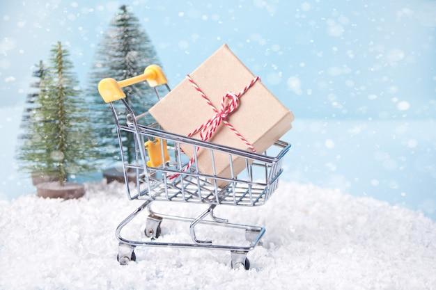 Composição de natal com carrinho de compras e caixa de presente, pinheiros no fundo.