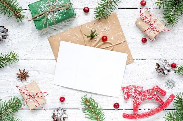 Composição de natal com cartão em branco. galhos de árvores de abeto, brinquedo de cavalo, caixas de presente e moldura de cones
