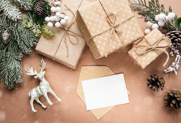 Composição de natal com cartão, veados, caixas de presente e ramos de abeto. vista superior, configuração plana.