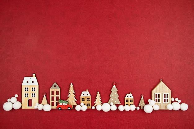 Composição de natal com casas de madeira de brinquedo, sobre o fundo vermelho