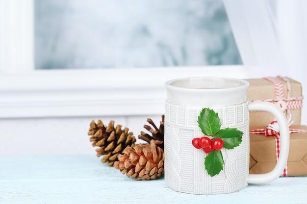 Composição de natal com copo de bebida quente, mesa de madeira