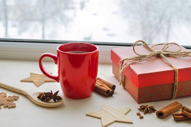 Composição de natal com copo vermelho de bebida quente no peitoril da janela de inverno