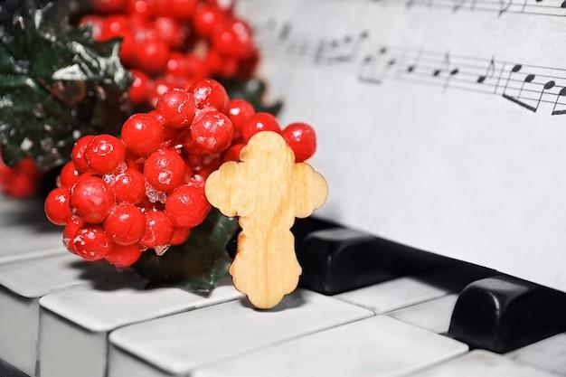 Composição de natal com cruz de madeira no piano, closeup