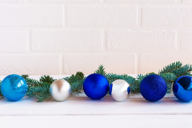 Composição de natal com enfeites azuis e silfer e galhos de pinheiro no fundo da parede de tijolo branco