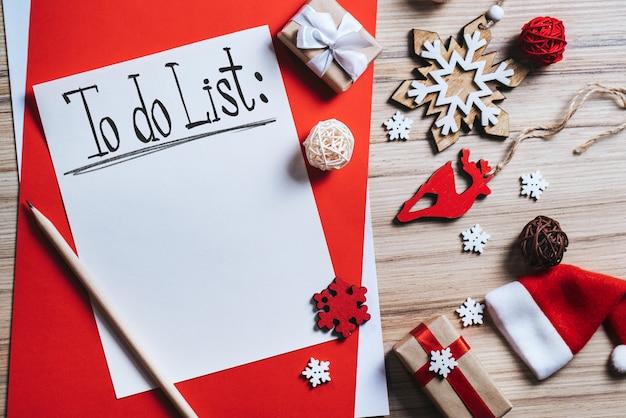 Composição de natal com enfeites de pinheiro e caixas de presente com um pedaço de papel branco e uma lista de tarefas
