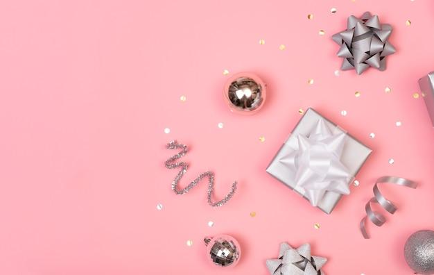 Composição de natal com enfeites e caixa de presente com confetes estrelas em pastel rosa. inverno. vista plana leiga, superior, copyspace.