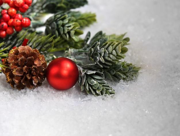 Composição de natal com enfeites e pinheiro na neve close-up