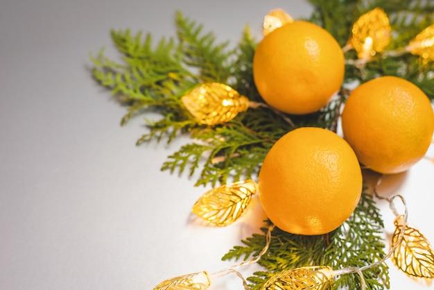 Composição de natal com frutas laranja, ramo de planta e guirlanda em fundo cinza