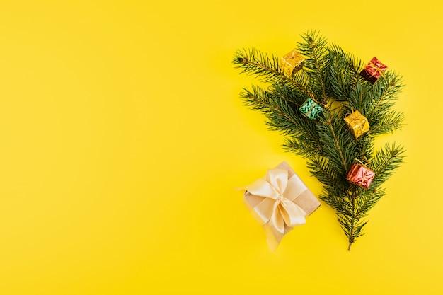 Composição de natal com galhos de árvores coníferas e caixa de presente em amarelo