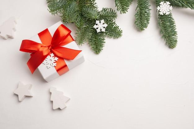 Composição de natal com galhos de pinheiro verde e caixa de presente branca, estrelas e flocos de neve em fundo branco de madeira.