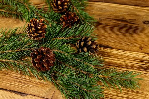 Composição de natal com galhos de pinheiros e cones em fundo de madeira.