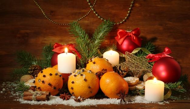 Composição de natal com laranjas e pinheiros, em fundo de madeira.