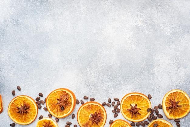 Composição de natal com laranjas secas, canela, anis e nozes em um fundo cinza de concreto.