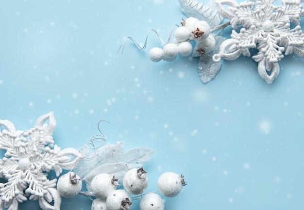 Composição de natal com moldura feita de decoração branca em superfície azul pastel