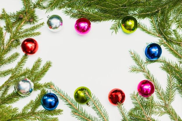Composição de natal com moldura vazia de bolas coloridas e galhos de árvore do abeto. ornamento, decorações de ano novo em fundo branco. modelo de cartão de cumprimentos de maquete com espaço de cópia, categoricamente, vista superior.