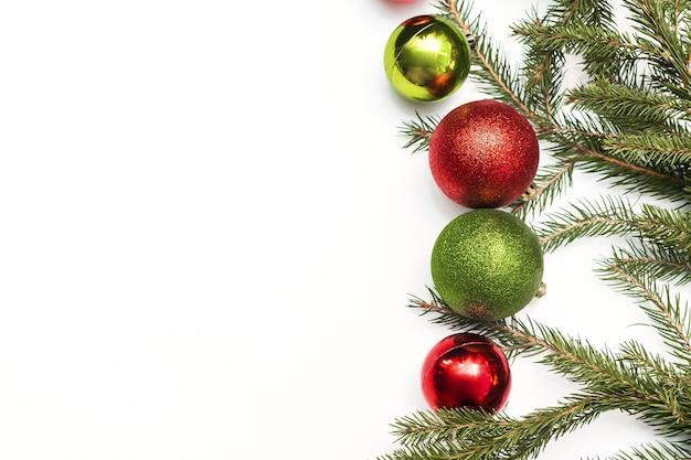 Composição de natal com moldura vazia de bolas verdes vermelhas coloridas e galhos de árvore do abeto. decorações de ano novo em fundo branco. modelo de cartão de felicitações de maquete com espaço de cópia, de maneira plana, superior