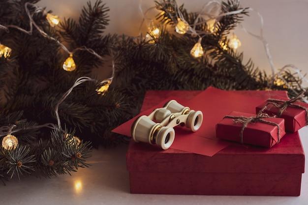 Composição de natal com óculos de ópera, ramo de abeto, caixas de presente vermelha e festão