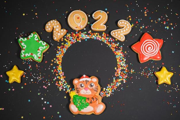 Composição de natal com pão de mel na superfície escura. cartão de humor de férias. vista superior, copie o espaço. tradições familiares, diy, conceito de celebração. fundo festivo com biscoitos caseiros de gengibre.