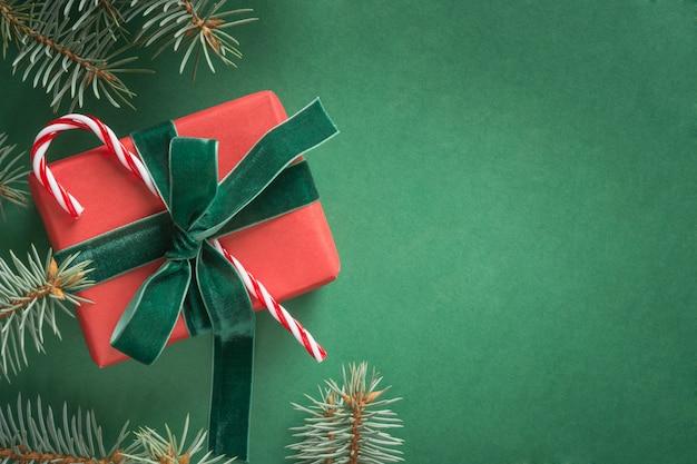 Composição de natal com presente vermelha e árvore de natal sobre fundo verde. cartão de felicitações feriado de inverno. feliz ano novo. vista de cima.
