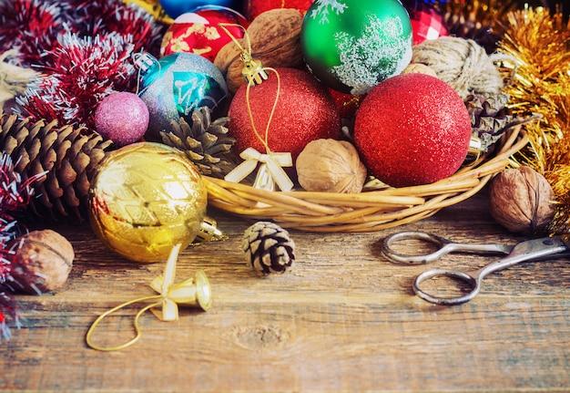 Composição de natal com presentes. cesta, bolas vermelhas, pinhas, flocos de neve na mesa de madeira. estilo vintage