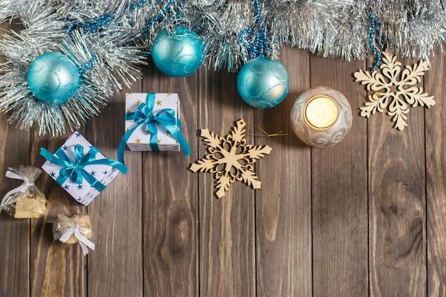 Composição de natal com presentes, velas e flocos de neve decorativos em fundo de madeira