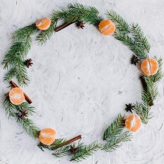 Composição de natal com raminhos de árvore, tangerinas, canela e anis em forma de círculo