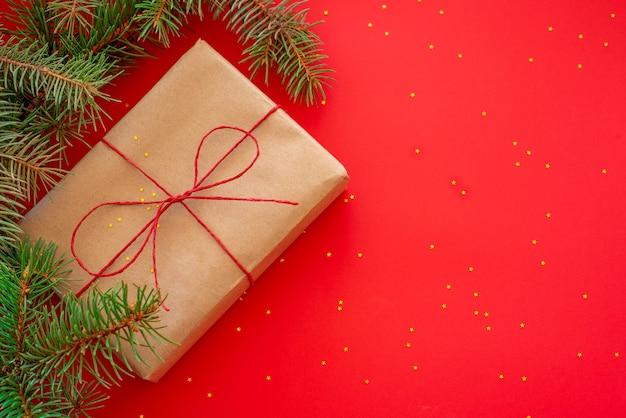 Composição de natal com ramos de pinheiro e um presente embrulhado em papel artesanal