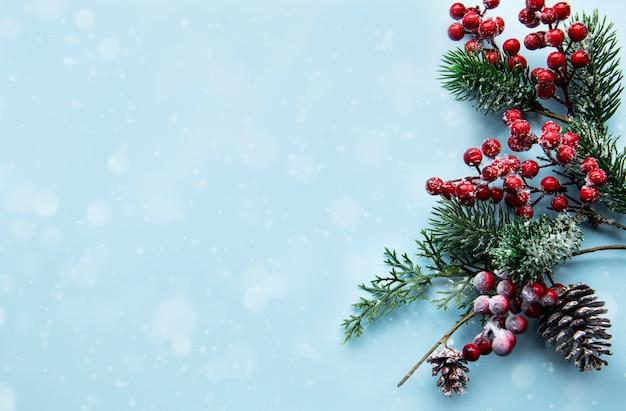 Composição de natal com ramos de pinheiro nevado em fundo azul pastel.