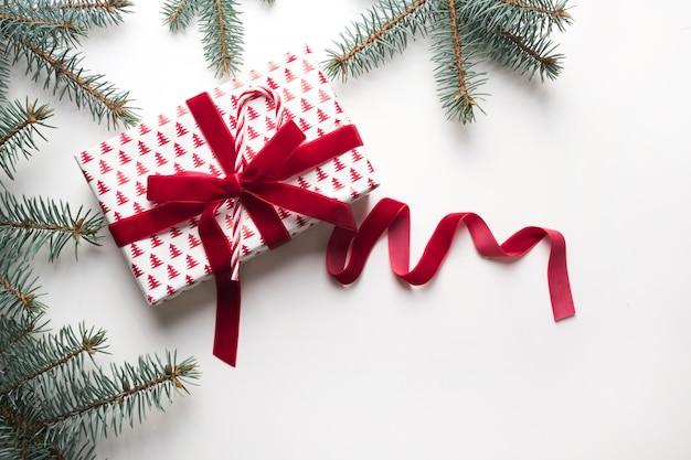 Composição de natal com ramos de presente e abeto vermelhos. cartão de felicitações feriado de inverno. feliz ano novo. espaço para texto. vista de cima.