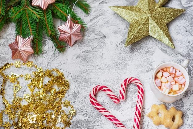 Composição de natal com ramos verdes de abeto, guirlanda de ano novo, brinquedos, copo com marshmallows e pirulitos