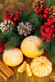 Composição de natal com tangerinas maduras foscas em fundo de madeira.