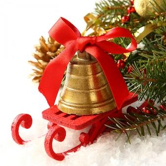 Composição de natal com trenó e sino de ouro sobre branco