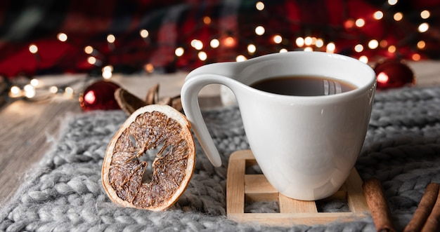 Composição de natal com uma xícara de chá, laranjas secas, especiarias em um fundo desfocado.
