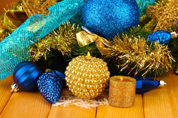Composição de natal com velas e enfeites nas cores azul e dourado sobre fundo de madeira.
