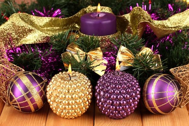 Composição de natal com velas e enfeites nas cores roxa e dourada em superfície de madeira