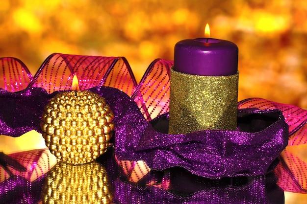 Composição de natal com velas e enfeites nas cores roxa e dourada